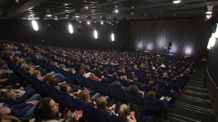 Vor einem vollen Kinosaal stehen ein Mann und eine Frau auf einer Bühne