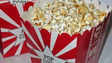 """zwei überbordend befüllte Popcorn-Becher mit der Aufschrift """"Popcorn"""""""