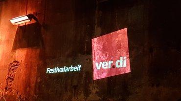 Logo der Festivalarbeiter*innen in ver.di projiziert  auf eine Wand in der Kulturbrauerei Berlin