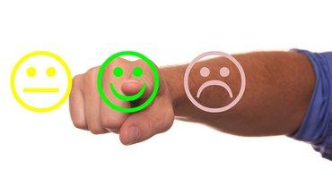Eine Hand tippt auf einen grünen lächelnden Smiley. Rechts und links daneben befinden sich ein neutraler und ein trauriger Smiley