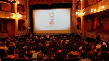 Blick auf eine Kinoleinwand, im Vordergrund ein voll besetzter Kinosaal